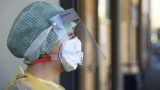 A healthcare worker wearing a protective mask