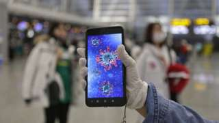 A passenger shows an illustration of the coronavirus on his mobile phone at Guangzhou airport in Guangzhou, Guangdong Province, China, 23 January 2020