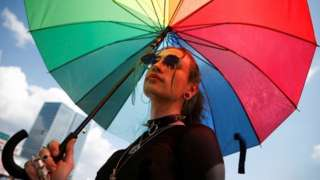 Protester holds rainbow umbrella during Warsaw pride march