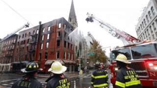 Firefighters stand in front of Middle Collegiate Church after a blaze gutted the building