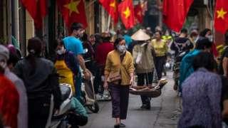 Mujer en Vietnam con mascarilla en marzo.