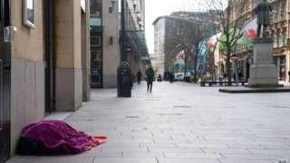 Person digartref ar y stryd yng nghanol Caerdydd cyn y pandemig