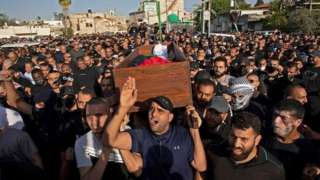 Warga Palestina mengangkat keranda jenazah saat pemakaman di dalam kota Lod di Israel tengah dekat Tel Aviv.