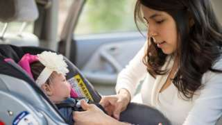 Mother strapping young baby girl into car seat