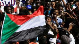 Des gens au rassemblement à Khartoum avec le drapeau soudanais