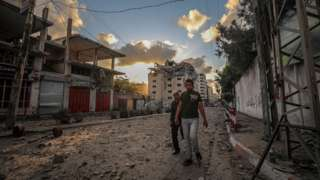 Palestinians walk past a destroyed building in Gaza City on 17 May 2021