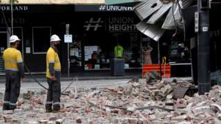 Emergency and rescue officials examine a damaged building in the popular shopping Chapel Street in Melbourne on September 22, 2021, after a 5.9 magnitude earthquake