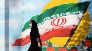 伊朗德黑兰街头一名戴着口罩的女子走过一幅伊朗国旗壁画(28/7/2020)