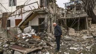 An elderly man stands in front of a destroyed house after shelling in the breakaway Nagorno-Karabakh region's main city of Stepanakert