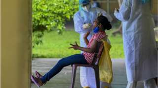 A resident reacts as a health worker collects a swab sample for the Covid-19 coronavirus