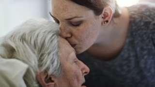 Una anciana recibe un beso en la frente