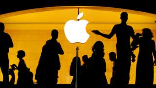 Silhouetted figures by the Apple logo