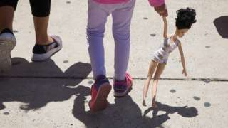 A 4-year-old Honduran girl carries a doll while walking with her immigrant mother