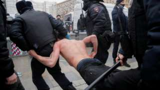 Law enforcement officers detain and drag topless man during a rally in Moscow