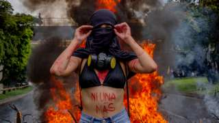 A protester stands in front of a fire during a protest in Medellín, Colombia, on 18 May 2021