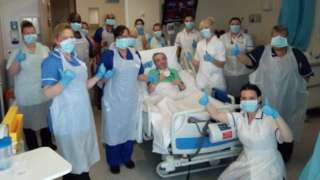 Paul in bed surrounded by medical staff