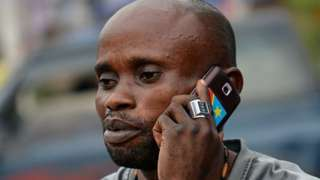 A local resident uses a mobile phone in Kinshasa on February 4, 2015