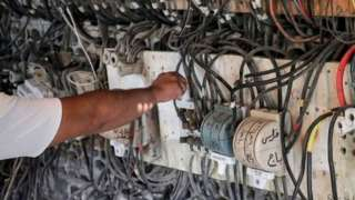 A technician controls an electric switchboard connecting homes to electricity generators in a suburb of Lebanon's capital Beirut, on June 23, 2021.