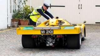 Traffic warden putting parking ticket on Ferrari