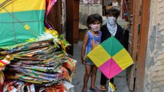 Children in Delhi holding a kite