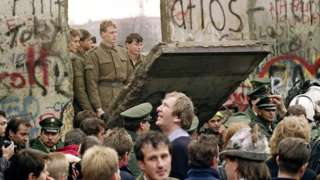 West Berliners crowd in front of the Berlin Wall early 11 November 1989 as they watch East German border guards demolishing a section to open a new crossing point between East and West Berlin