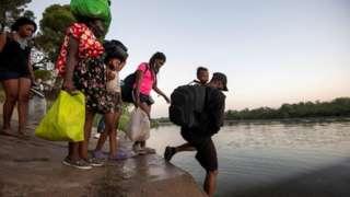 Migrants cross the Rio Grande on the US - Mexico border