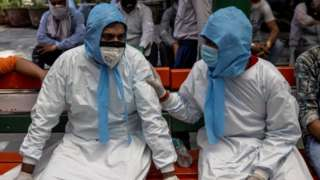 Two men sit together in PPE