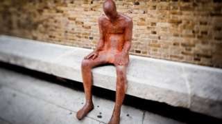 Life-sized sculpture sitting on a concrete bench