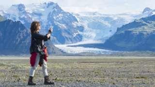 Mulher tira foto de paisagem com montanhas e neve na Islândia