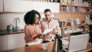 Couple dey look bills for front of computer