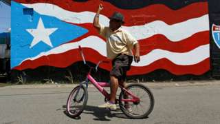A man in front of a painting of a Puerto Rico flag