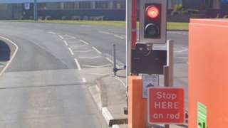 Red traffic light and sign saying Stop Here on Red at a Tyne Tunnel barrier-free lane