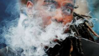 A demonstrator vapes during a protest of all vaping product sales in Boston, Massachusetts