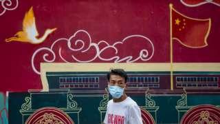 上海街头一位戴着口罩的男子走过一面中国形象宣传壁画(6/8/2020)