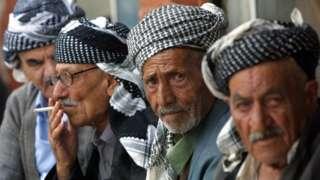 Elderly Iraqi Kurdish men in traditional Kurdish garb sit in the bazaar of Suleimaniyeh, the Patriotic Union of Kurdistan (PUK)-controlled city, some 340km northeast of Baghdad, 17 October 2002