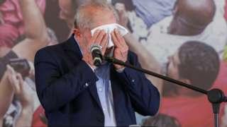 Em pé e em frente a microfone, Lula enxuga testa