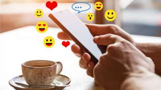 Two hands holding a mobile phone with emoji symbols