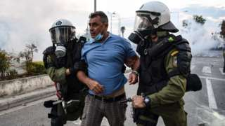 Riot police detain a protester during a demonstration in Thessaloniki against the agreement reached by Greece and Macedonia to resolve a dispute over the former Yugoslav republic's name, 8 September 2018