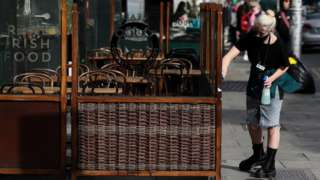A restaurant worker cleans an outdoor seating area in Dublin