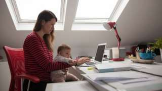 Woman working from home with baby.