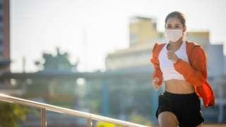 Mulher jovem correndo com roupa de ginástica e máscara branca