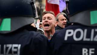 A protester shouts at police officers during a demonstration against German coronavirus restrictions, in Berlin, Germany, 18 November 2020