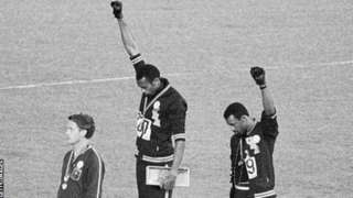 The iconic image of Tommie Smith (centre) and John Carlos (right) with black-gloved fists raised on the podium at the 1968 Olympic Games in Mexico City
