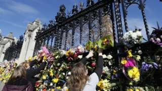 People place flowers outside Parliament