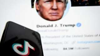 TikTok logo on phone in front of Donald Trump's Twitter feed on a PC screen.