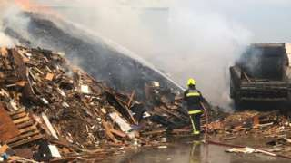 Firefighter blasts water onto woodpile