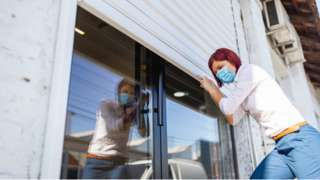 Woman shuttering a shop