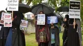 팻말을 든 시위대가 학교 앞에서 성 소수자 포용 교육 반대 시위를 벌이고 있다