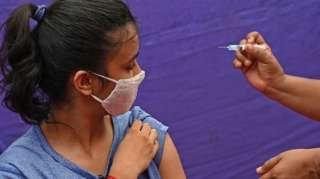A health worker prepares a jab of the Covishield' Covid-19 coronavirus vaccine before inoculating a girl at a vaccination camp held in a residential area in Chennai on May 20, 2021