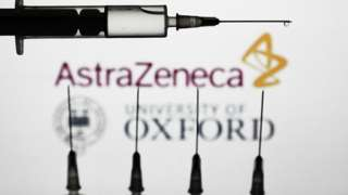 cinco vacinas com logomarca da farmacêutica AstraZeneca e da Universidade de Oxford ao fundo